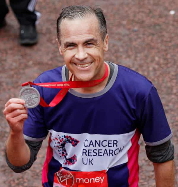 Mark Carney, the governor of the Bank of England, poses with his medal after running the London Marathon