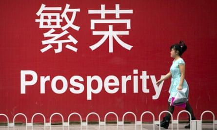 """A woman walks past a sign reading """"prosperity"""" in Beijing"""