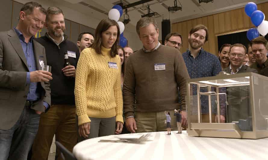 Matt Damon and Kristen Wiig looking at their miniatures in Downsizing