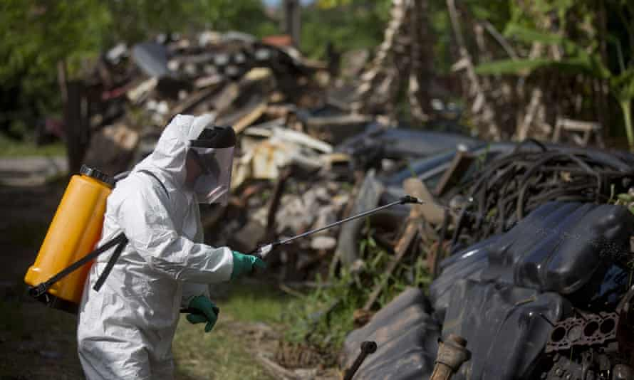 A municipal health worker sprays insecticide in a junkyard to combat the Aedes aegypti mosquito that transmits the Zika virus, in Joao Pessoa, Brazil.