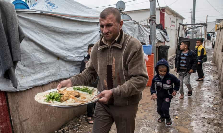 Man, with dish of food, and children walking through mud at Debaga camp