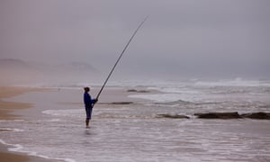 A fisherman on Tergniet Rheebok beach in Mossel Bay, South Africa.