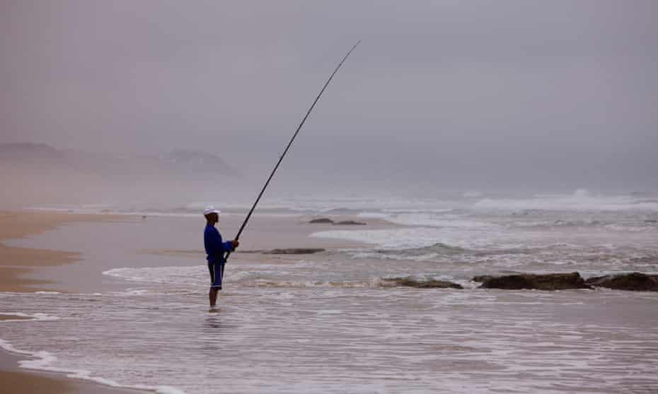A fisherman on Tergniet Rheebok beach in Mossel Bay, South Africa.
