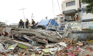 Police officers stand on debris in Tarqui neighborhood in Manta A