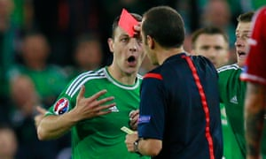 Northern Ireland's Chris Baird is shown a red card after receiving two yellow cards for two fouls in under 10 seconds.