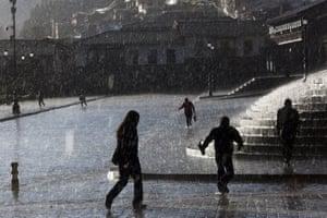 People walk through heavy rain in Cusco, the historic capital of the Inca empire