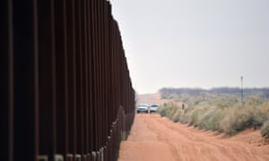 Border patrol vehicles drive next to a US-Mexico fence in the booming New Mexico town of Santa Teresa on 5 January 2016.