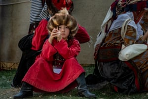 A young Kyrgyz girl wearing traditional dress watches over the activities and spectators at the World Nomad Games