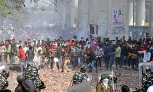 Protesters throw stones at police in eastern Delhi on Monday. Five people died in violence across the capital.