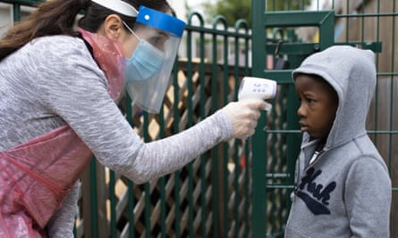 A member of staff takes a child's temperature at the Harris Academy's Shortland's school in London. The Delve report stresses the need for thorough hygiene and social distancing in schools.