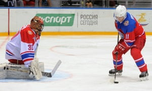 Russian President Vladimir Putin (R) takes part in a gala game of the Night Ice Hockey league tournament in Sochi.