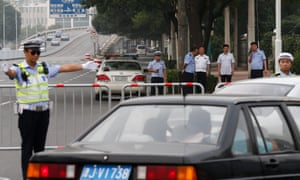Chinese police and security personnel look on from a distance as traffic is diverted away from a road leading to the No 2 Intermediate People's Court in Tianjin City.