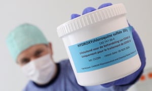 A pharmacist displays a box of hydroxychloroquine
