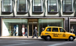 A yellow London taxi cab operated by Hailo stands outside store in 2014.
