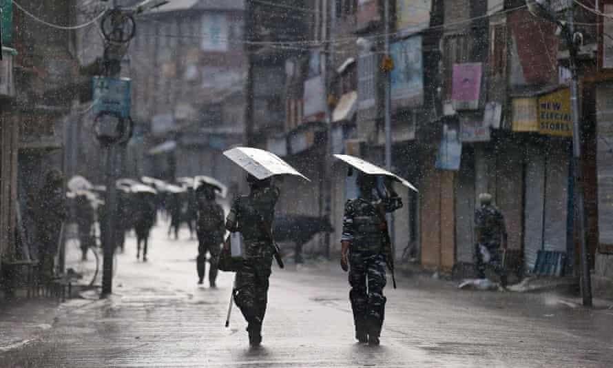 Armed Indian security forces personnel patrol a deserted street in Srinagar August.