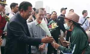 Cambodia's Prime Minister Hun Sen, left, gives a bouquet of flowers to a passenger who disembarked from the MS Westerdam.