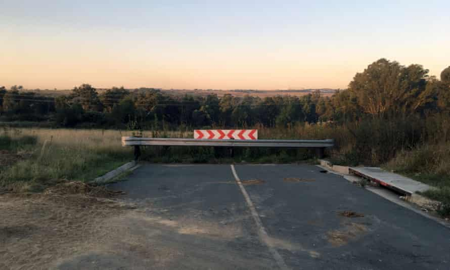 Footprint of a city that never was: a road ends abruptly in a barrier, with the Modderfontein nature reserve behind