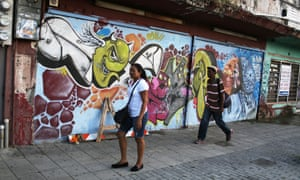 Puerto Ricans walk past a shuttered business in San Juan.