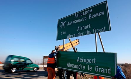 Workers remove a road sign with the former name of Skopje's airport.