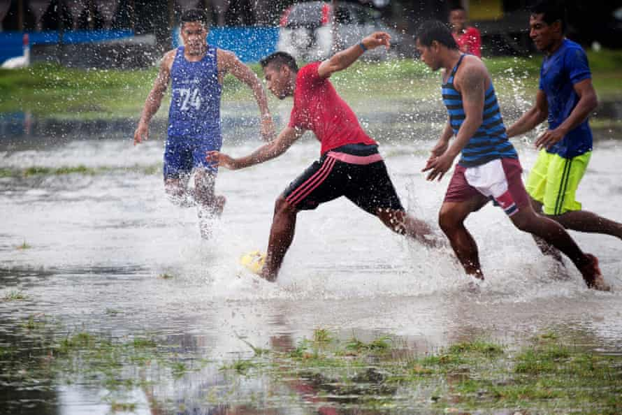 A local derby football match played at the main stadium in Bairiki, South Tarawa, on a flooded pitch.