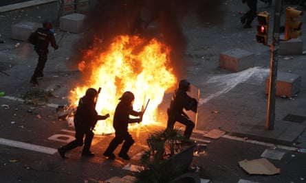 Riot police officers run past a burning barricade in Barcelona.