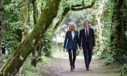 Emmanuel Macron walks with his wife Brigitte Macron in the park of the newly restored Chateau de Ferney.