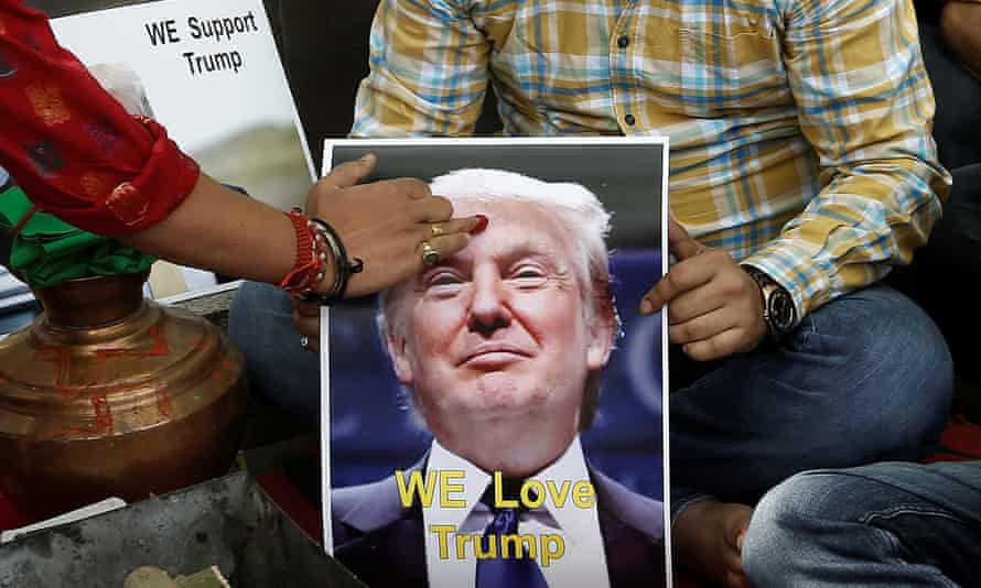 A priest applies a tika on the portrait of Donald Trump during a special prayer to ensure his victory, in New Delhi on Wednesday.