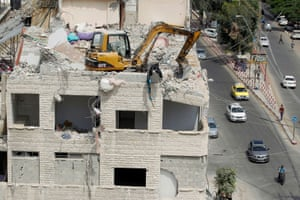 Gaza City: a machine removes debris from a building damaged in Israeli air strikes