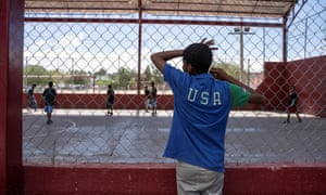 A resident of a migrant shelter watches a soccer match at a nearby park on 9 June.