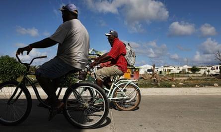 Men ride bicycles on 8 December 2017 in Cordington, Barbuda.