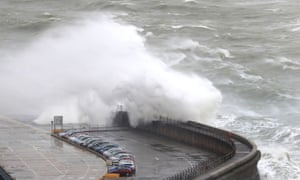 Waves crash over the harbour arm at Dover in Kent