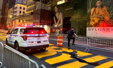 A police officer guards the Black Lives Matter mural at Trump Tower after it was vandalized with black paint.
