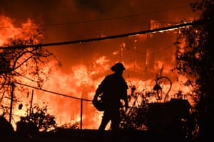 A firefighter is silhouetted by a burning home in California during a wildfire