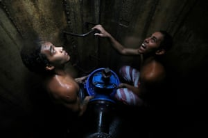 Caracas, Venezuela Boys collect water from an underground main pipeline during a disruption to water supplies due to a power outage