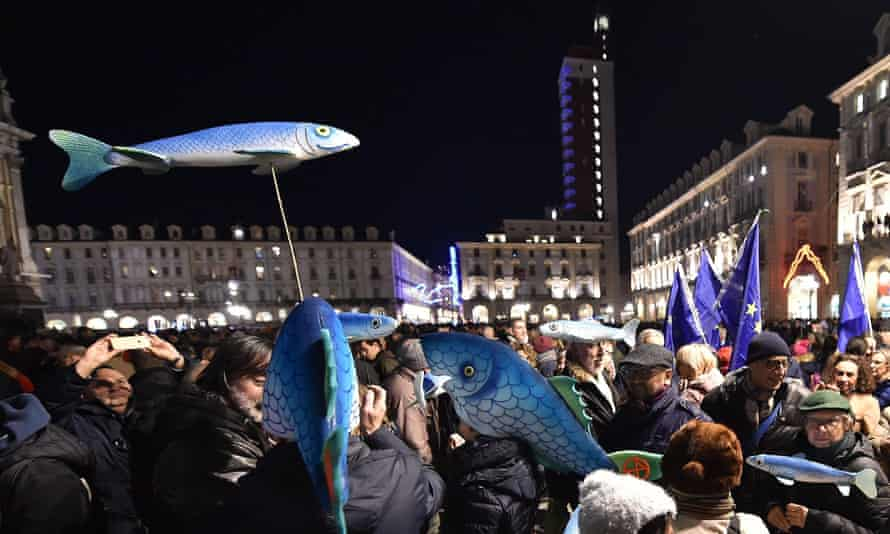 Sardine signs are held in the air at the Turin protest.