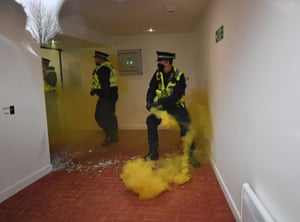 Police officers deal with a flare that was thrown through a window at Old Trafford.