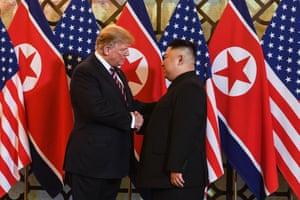 Donald Trump shakes hands with Kim Jong-un