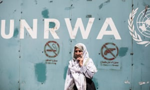 An elderly female protester stands outside the gate of the UN Relief and Works Agency office in Gaza