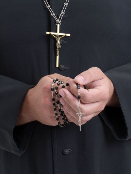 a figure wearing a black cassock with a gold crucifix holding black rosary beads in clasped hands