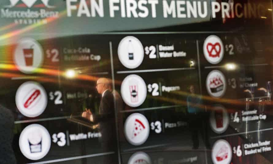 Rich McKay, the Atlanta Falcons president and CEO, stands in front of a screen with proposed concession stand menu prices.