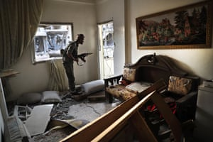 A US-backed Syrian democratic forces fighter takes up a position inside a destroyed apartment on the frontline of the battle for the city.