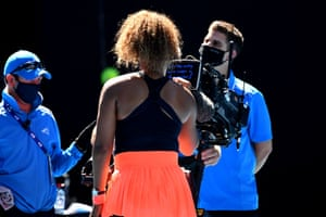 Naomi Osaka signs the camera before heading off-court.