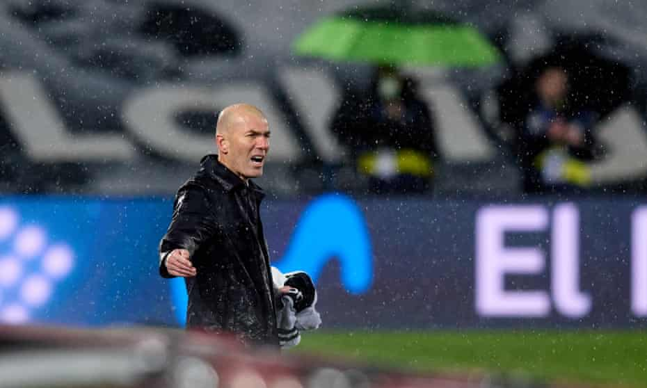 Zinedine Zidane watches his Real Madrid team in the rain against Barcelona