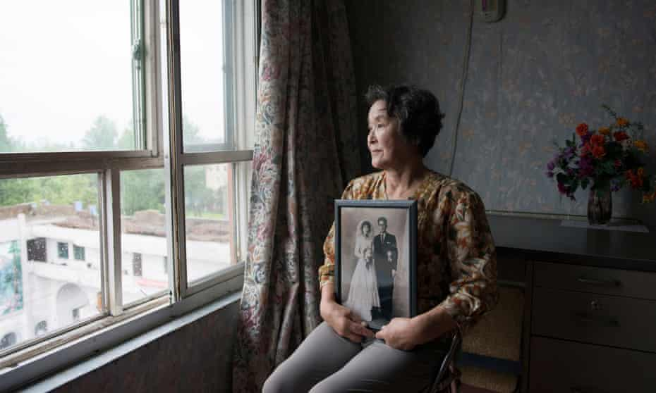Mitsuko Minakawa, 77, with her wedding photograph; the couple moved to North Korea in 1960.