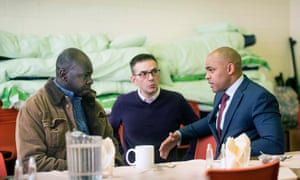 The mayor of Bristol, Marvin Rees (right) at a church hall in the city talking to homeless man Emile (left) from Chad with Jonathan Lee of Crisis Centre Ministries.