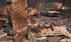 A vintage Jaguar car sits in ruins after a bushfire destroyed a property in Old Bar, NSW