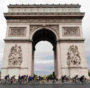 The riders with the yellow jersey pass the Arc de Triomphe.