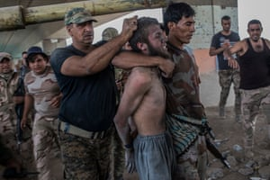 A man suspected of being an Islamic State militant is detained by the Iraqi Army in the Old City of Mosul, Iraq