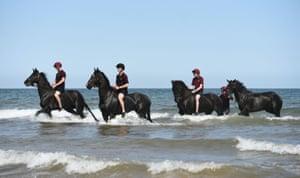 Troops perform exercises in the sea on horseback in Norfolk