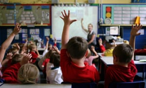 Children in a classroom raising their hands, as teacher also raises hers.